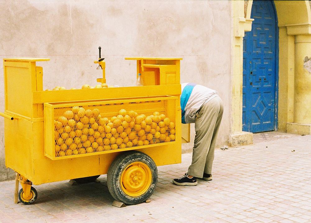 val carcary green yellow orange cart with man bending blue door essaouira